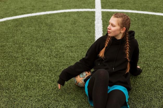 Adolescente in posa con una palla all'aperto