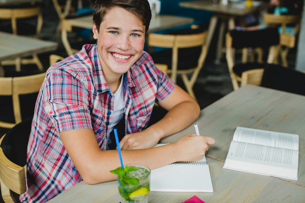 Teenager posing with notepad at table