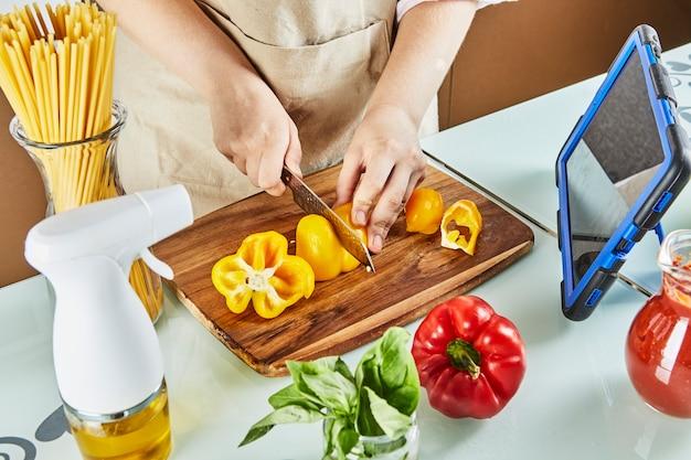 ティーンエイジャーは、仮想オンラインセミナーを準備し、黄ピーマンをカットし、自宅のキッチンで健康的な食事を準備しながら、タッチスクリーンタブレットでデジタルレシピを確認します。
