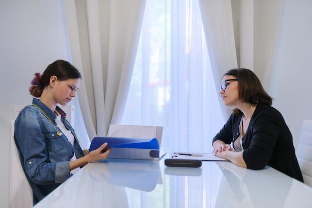 10代の心理学者、10代の少女と話している女性のソーシャルワーカー