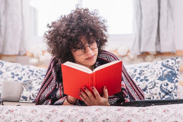 Libro di lettura dell'adolescente sul letto