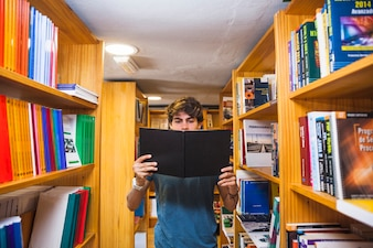 Teenager reading book between bookcases