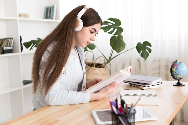 Teenager reading book with headphones on