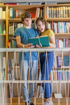 Teenager reading book with shocked girlfriend
