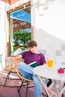 屋外カフェで読むティーンエイジャー