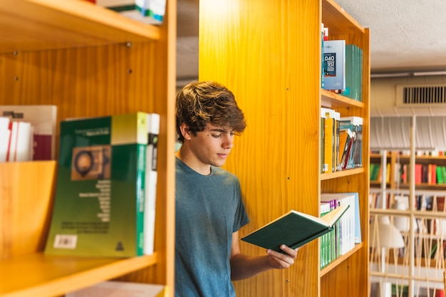 Teenager reading between two bookcases