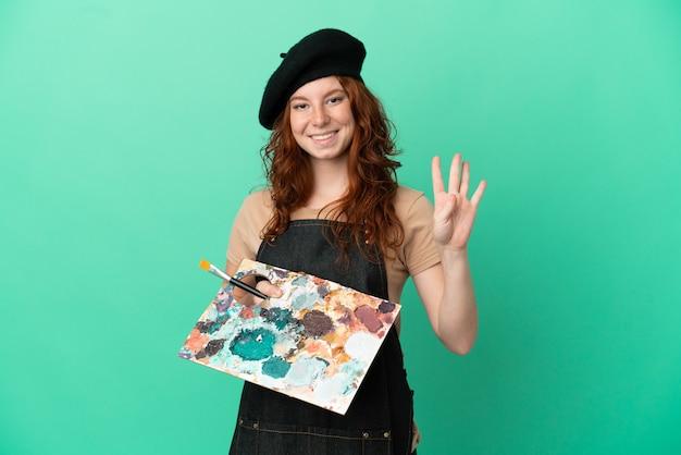幸せな緑の背景に分離されたパレットを保持し、指で4を数えるティーンエイジャーの赤毛アーティスト