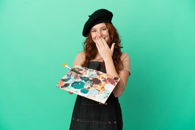 緑の背景に分離されたパレットを保持しているティーンエイジャーの赤毛のアーティストは、手で口を覆って幸せと笑顔