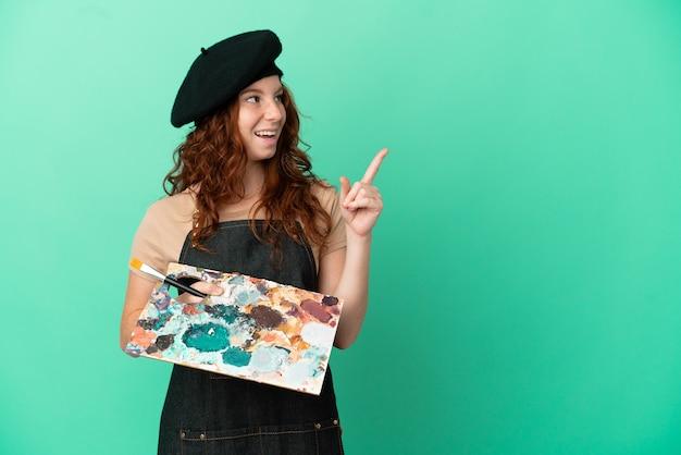 Рыжий художник-подросток держит палитру, изолированную на зеленом фоне, намеревается реализовать решение, подняв палец вверх