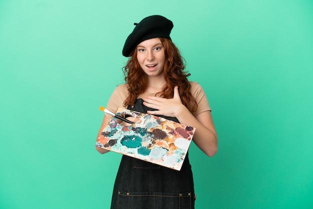 緑の背景に分離されたパレットを保持しているティーンエイジャーの赤毛のアーティストは、右を見ながら驚いてショックを受けました