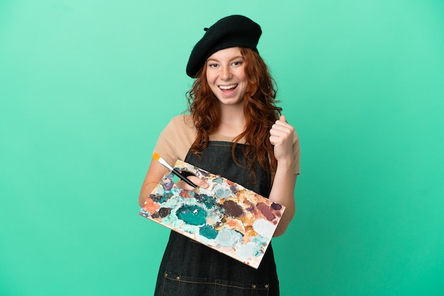 Teenager redhead artist holding a palette isolated on green background celebrating a victory in winner position