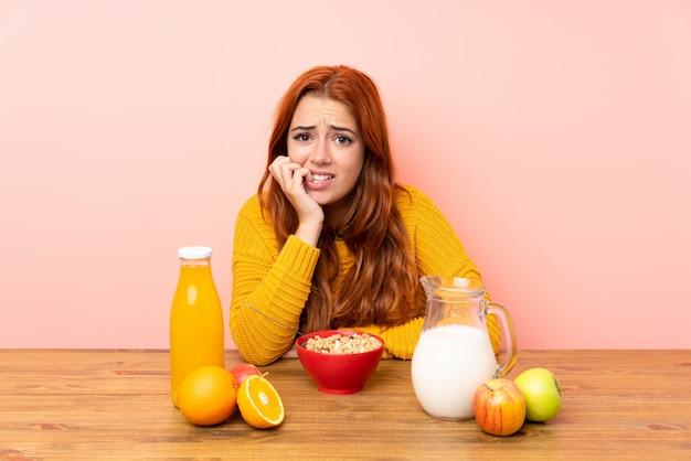 Рыжая девушка-подросток завтракает в столе нервной и напуганной