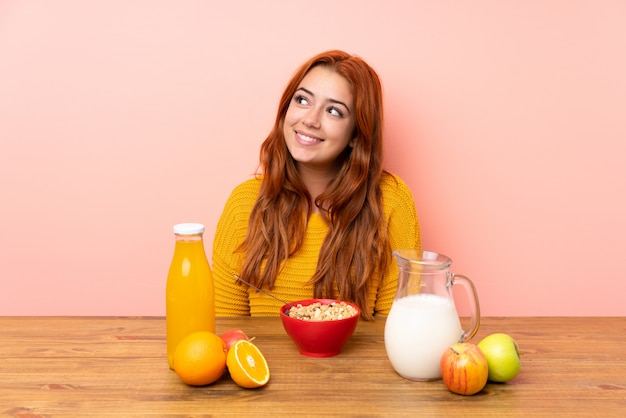 Teenager redhead girl having breakfast in a table laughing and looking up