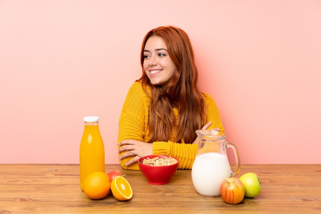 Teenager redhead girl having breakfast in a table looking to the side