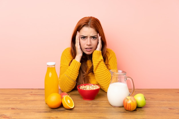 Teenager redhead girl having breakfast in a table unhappy and frustrated with something. negative facial expression