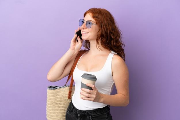 持ち帰り用のコーヒーと携帯電話を保持している紫色の背景に分離されたビーチバッグを保持しているティーンエイジャーの赤毛の女の子