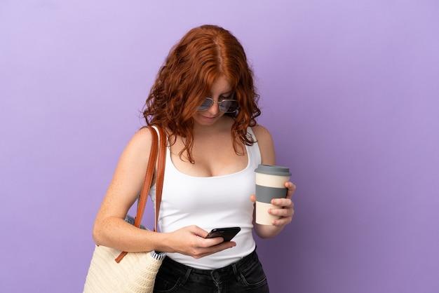 Рыжая девушка-подросток держит пляжную сумку, изолированную на фиолетовом фоне, держит кофе на вынос и мобильный