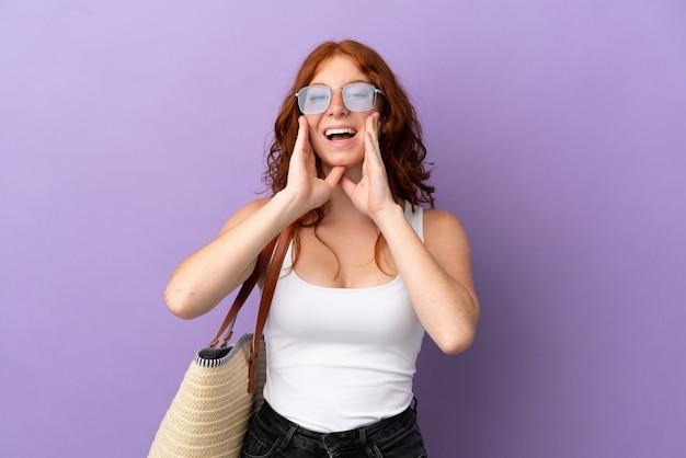 Рыжая девушка-подросток держит пляжную сумку, изолированную на фиолетовом фоне, кричит и что-то объявляет