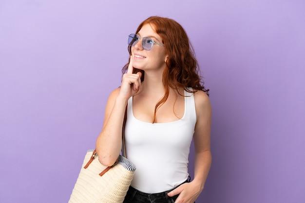 Рыжая девушка-подросток держит пляжную сумку на фиолетовом фоне, думая об идее, глядя вверх