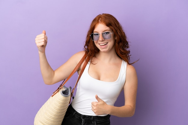 Teenager redhead girl holding a beach bag isolated on purple background making guitar gesture