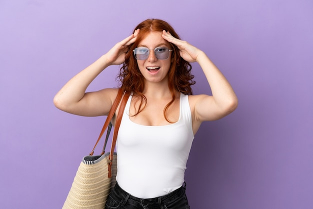 Teenager redhead girl holding a beach bag isolated on purple background with surprise expression