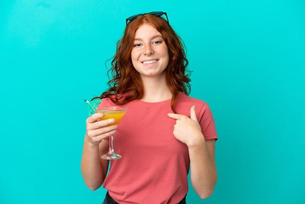 驚きの表情で青い背景に分離されたカクテルを保持しているティーンエイジャーの赤毛の女の子
