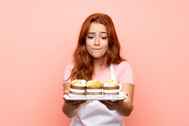 Teenager redhead girl holding lots of different mini cakes over isolated pink