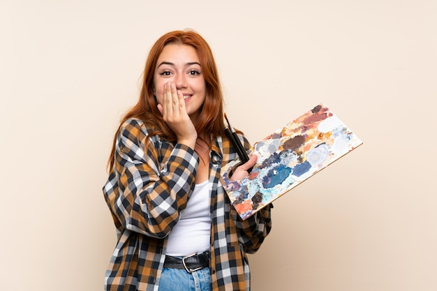 Teenager redhead girl holding a palette over isolated  with surprise facial expression