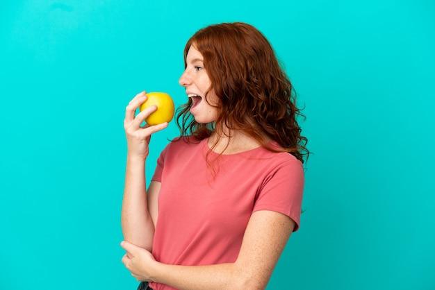 Рыжая девушка-подросток, изолированные на синем фоне, ест яблоко