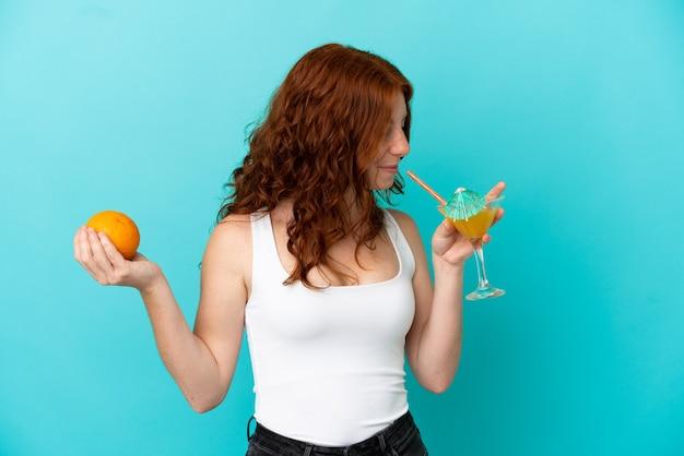 水着とカクテルを保持している青い背景に分離されたティーンエイジャーの赤毛の女の子