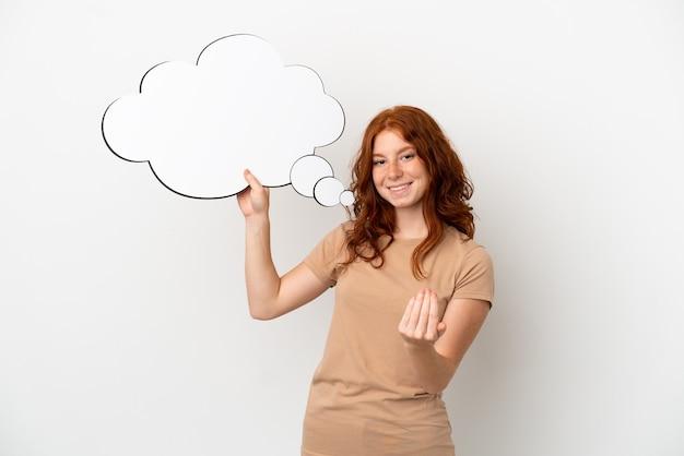 思考の吹き出しを保持し、来たるジェスチャーをしている白い背景で隔離のティーンエイジャーの赤毛の女の子