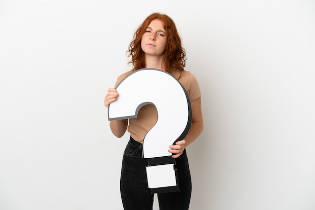 Teenager redhead girl isolated on white background holding a question mark icon and with sad expression