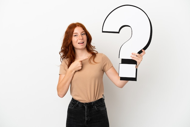 Teenager redhead girl isolated on white background holding a question mark icon with surprised expression