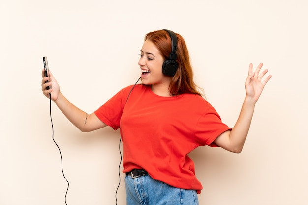 Teenager redhead girl listening music with a mobile over isolated