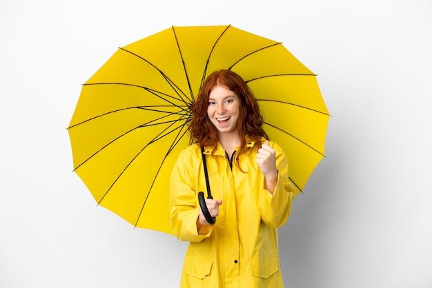 10대 빨간 머리 소녀 방수 코트와 우산은 우승자 위치에서 승리를 축하하는 흰색 배경에 고립
