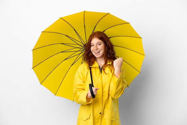 10대 빨간 머리 소녀 방수 코트와 우산은 승리를 축하하는 흰색 배경에 고립