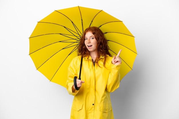 Рыжая девушка-подросток непромокаемое пальто и зонтик, изолированные на белом фоне, намереваясь реализовать решение, подняв палец вверх