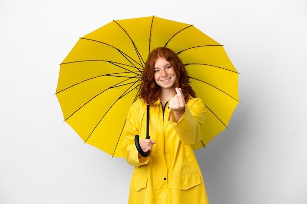Рыжая девушка-подросток непромокаемое пальто и зонтик, изолированные на белом фоне, делая денежный жест
