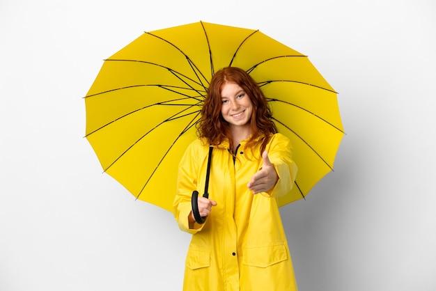 Рыжая девушка-подросток непромокаемое пальто и зонтик на белом фоне пожимает руку для заключения хорошей сделки