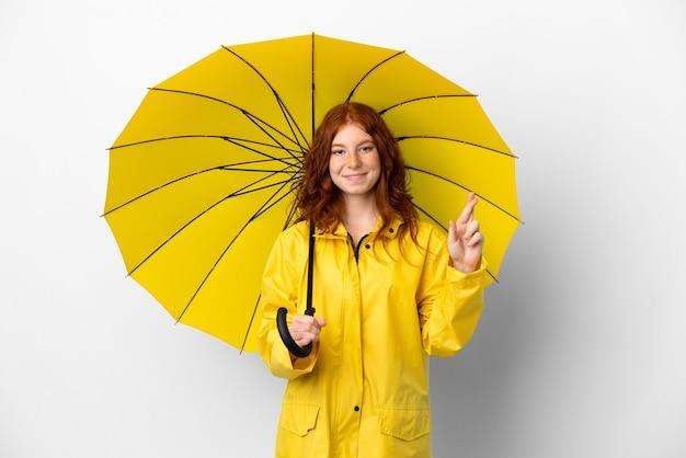 10대 빨간 머리 소녀의 방수 코트와 우산은 손가락으로 교차하고 최고를 바라는 흰색 배경에 고립