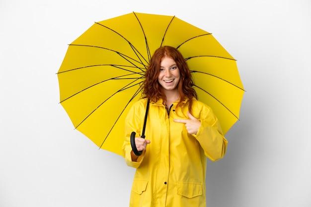驚きの表情で白い背景に分離されたティーンエイジャーの赤毛の女の子の防雨コートと傘