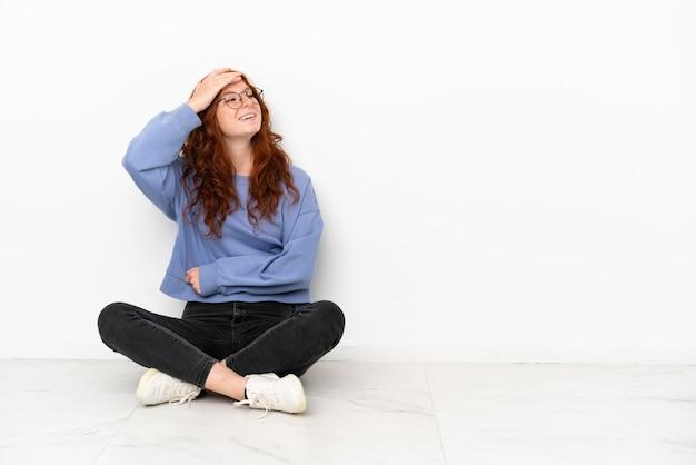Рыжая девушка-подросток, сидящая на полу на белом фоне, кое-что поняла и намеревается решить