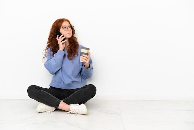 Рыжая девушка-подросток сидит на полу на белом фоне, держа кофе на вынос и мобильный