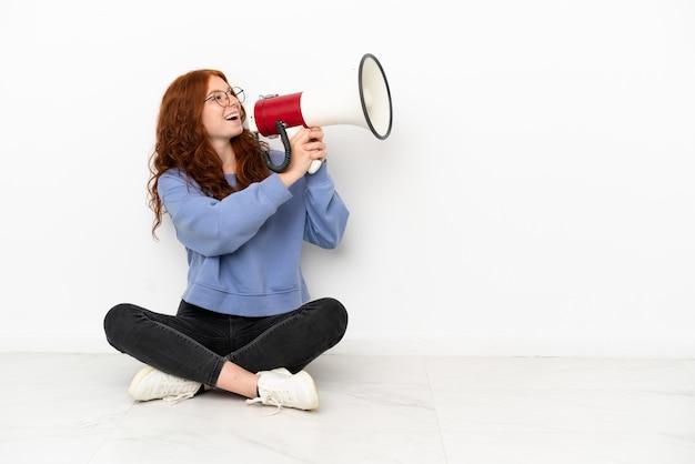 Рыжая девушка-подросток сидит на полу на белом фоне и кричит в мегафон