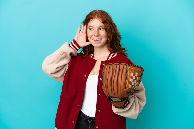 Teenager redhead girl with baseball glove isolated on blue background listening to something by putting hand on the ear