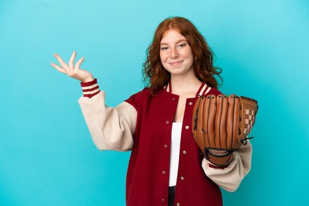 青い背景に分離された野球のグローブを持つティーンエイジャーの赤毛の少女は、来て招待するために手を横に伸ばします