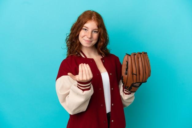 手で来るように誘う青い背景に分離された野球グローブを持つティーンエイジャーの赤毛の女の子。あなたが来て幸せ