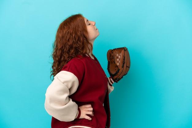 努力をしたために腰痛に苦しんでいる青い背景に分離された野球グローブを持つティーンエイジャーの赤毛の女の子