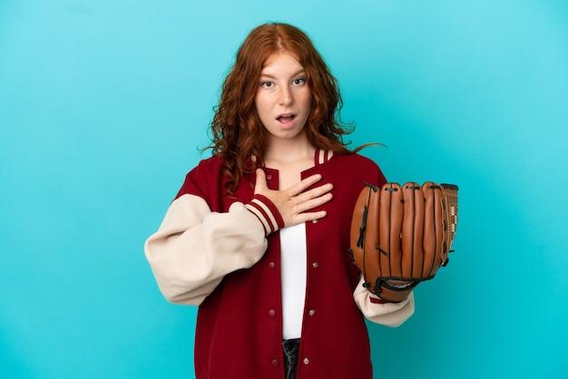青い背景に分離された野球のグローブを持つティーンエイジャーの赤毛の少女は、右を見ながら驚いてショックを受けました