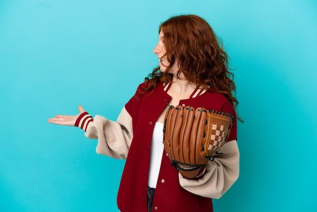 Рыжая девушка-подросток с бейсбольной перчаткой изолирована на синем фоне с удивленным выражением лица, глядя в сторону